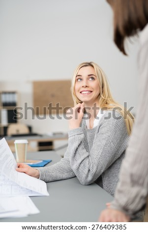 Smiling young businesswoman chatting to a co-worker looking up attentively as they have a discussion - stock photo