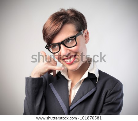 Smiling young businesswoman gesturing to call - stock photo