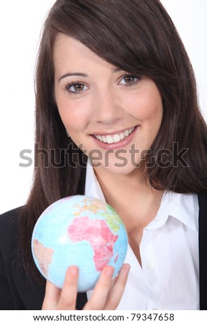 Smiling young businesswoman holding a globe - stock photo