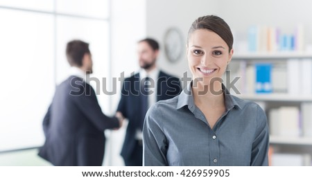 Smiling young businesswoman posing in the office, her colleagues are standing in the background