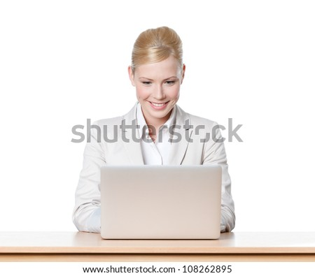 Smiling young businesswoman sitting at a office table with laptop, isolated - stock photo