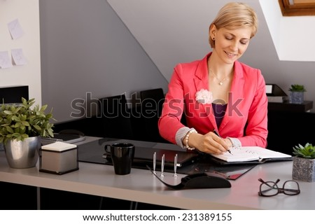 Smiling young businesswoman sitting at desk in office, writing notes. - stock photo