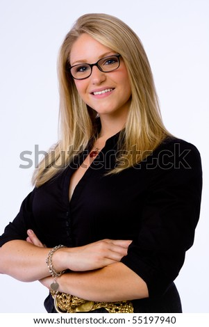 Smiling young businesswoman stands with arms crossed and looks at camera. - stock photo