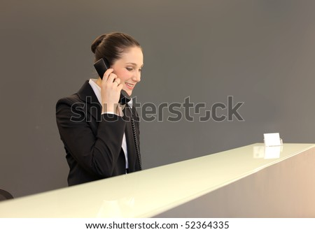 Smiling young businesswoman talking at the telephone at a reception