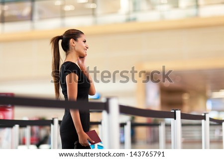 smiling young businesswoman talking on her cell phone at airport - stock photo