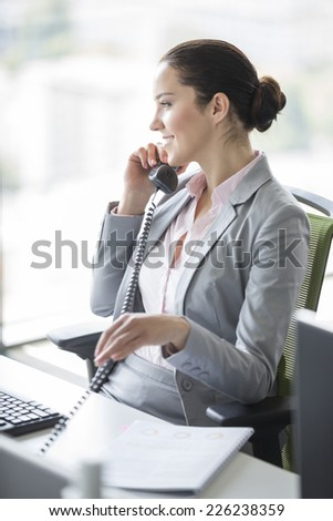 Smiling young businesswoman talking on landline phone in office - stock photo