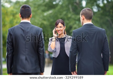 Smiling young businesswoman talking on the phone while meeting two businessmen on the street - stock photo
