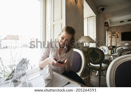 Smiling young businesswoman text messaging on cell phone at restaurant table - stock photo