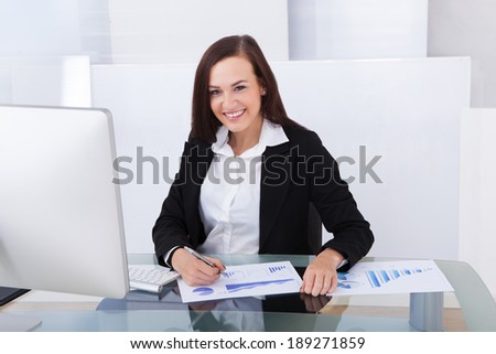 Smiling young businesswoman using computer at desk in office