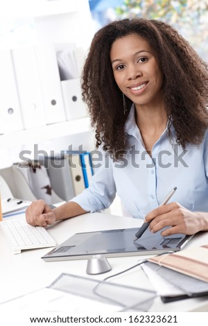 Smiling young businesswoman using drawing pad at desk. - stock photo