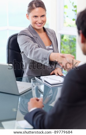 Smiling young businesswoman welcomes customer in her office - stock photo