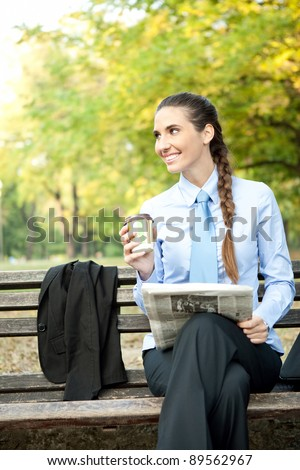 smiling young businesswoman with newspaper drinking coffee - stock photo