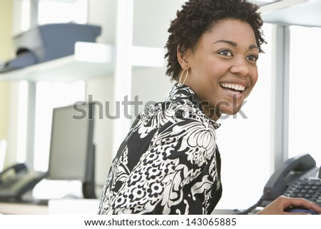 Smiling young businesswoman working at office desk - stock photo