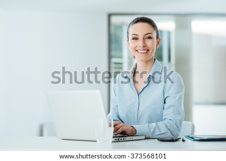 Smiling young businesswoman working at office desk and typing on a laptop, she is looking at camera - stock photo