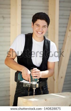 Smiling young carpenter enjoys doing his job - stock photo