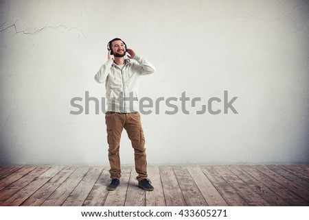 Smiling young Caucasian bearded man in casual clothes and headphones is standing in empty room with white wall and wooden floor - stock photo