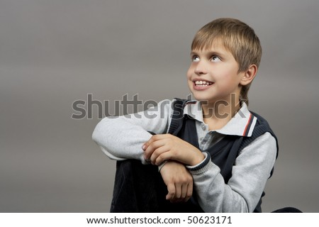 smiling young caucasian boy with calm face expression and looking up isolated over gray background - stock photo