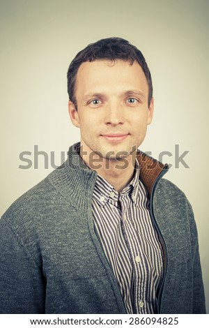 Smiling young Caucasian man in casual clothing, studio portrait with vintage tonal correction photo filter effect, instagram old style - stock photo