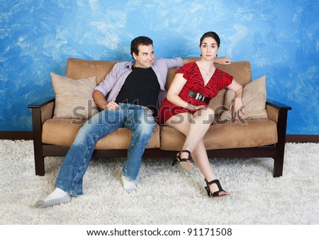Smiling young Caucasian man with frustrated woman sit on sofa - stock photo