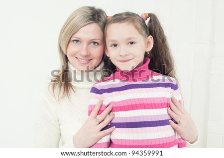 Smiling young caucasian woman embracing her 7-year old daughter