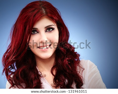 Smiling young caucasian woman in glamour closeup, over blue background