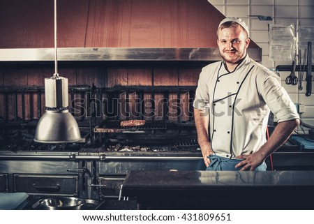 Smiling young chef in the kitchen interior - stock photo