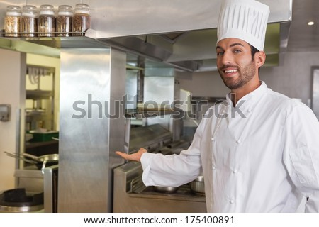 Smiling young chef looking at camera showing his workplace in a commercial kitchen - stock photo
