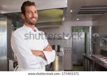 Smiling young chef standing with arms crossed in a commercial kitchen - stock photo