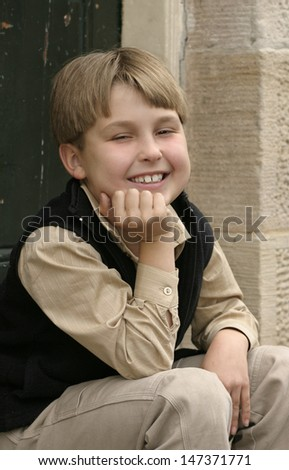 Smiling young child boy sitting on a doorstep - stock photo