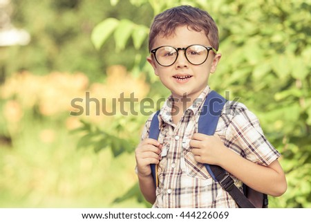 Smiling young  child in a  uniform standing against a tree in the park at the day time. Concept of the boy are ready to go to school. - stock photo
