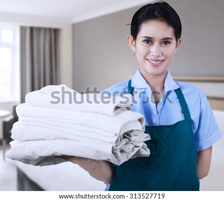 Smiling young cleaning lady holding towels in a hotel room - stock photo
