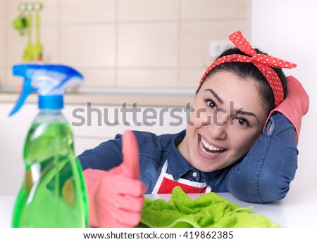 Smiling young cleaning lady with pink rubber gloves showing ok sign with thumbs up in the kitchen - stock photo