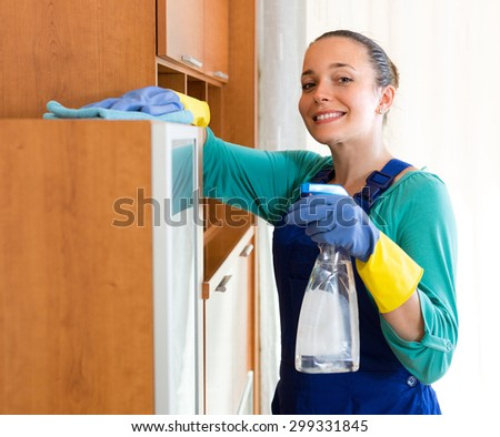 Smiling  young cleaning woman in uniform wiping furniture in the office  - stock photo