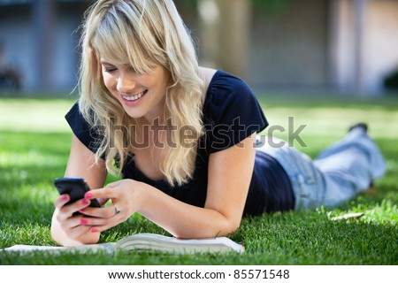Smiling young college girl texting on a cell phone - stock photo