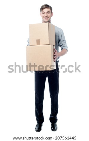 Smiling young corporate man carrying stack of boxes