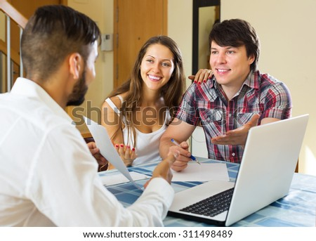 Smiling young couple and salesman talking cheerfully about purchase