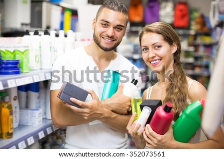 Smiling young couple buying detergents, shampoo and perfume in supermarket. Selective focus - stock photo