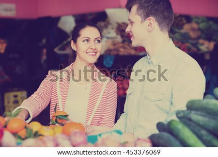 Smiling young couple choosing fruits and vegetables in market  - stock photo