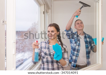 Smiling young couple cleaning windows in winter