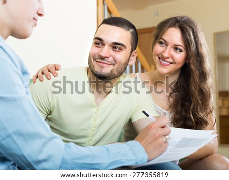 Smiling young couple discussing details of private insurance with agent