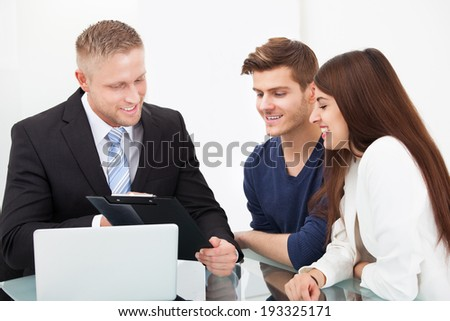 Smiling young couple discussing with financial advisor at office desk - stock photo