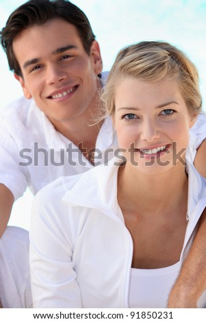 Smiling young couple dressed in white on a summer's day - stock photo