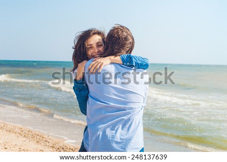 smiling young couple embracing and having fun on a summer beach - stock photo