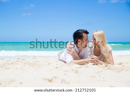 Smiling young couple embracing and lying at beautiful summer sandy beach - stock photo
