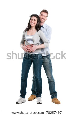 Smiling young couple embracing and standing full length isolated on white background - stock photo