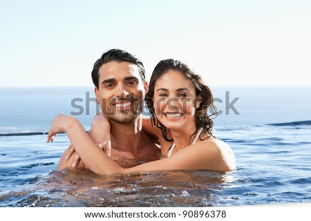 Smiling young couple embracing in the pool