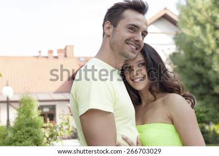 Smiling young couple embracing outdoors - stock photo