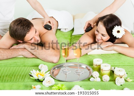 Smiling young couple enjoying hot stone massage at beauty spa - stock photo
