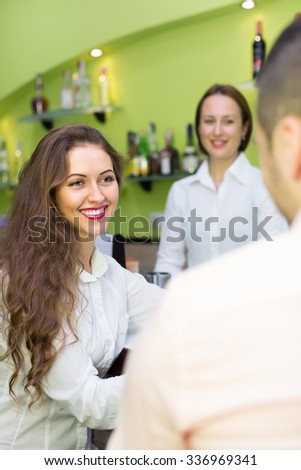 Smiling young couple having a date with wine at bar. Focus on girl