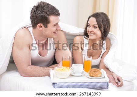 Smiling young couple having breakfast in bed.